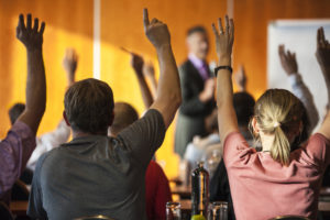 Rear view of a group of people attending a seminar or occupational training, all raising hands.